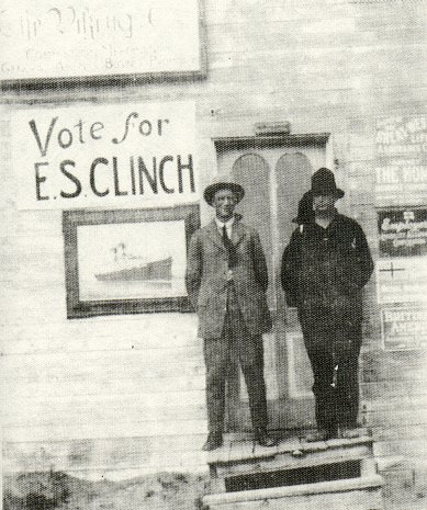 Mr. C.E. Craddock and Mr. Vego Neilson with Mr. Craddock's signs in the background.