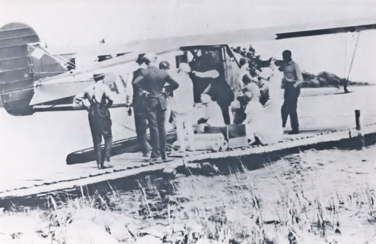 Reverend Charlie Hives and All Saints Anglican Mission staff boarding Cherry Red Airlines Buhl biplane in 1929.