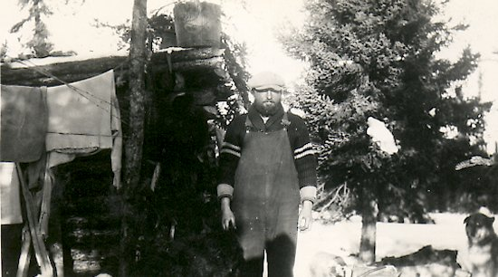Ed Theriau in front of his trapping cabin