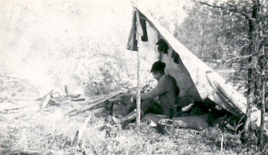Fred Darbyshire under lean-to camp
