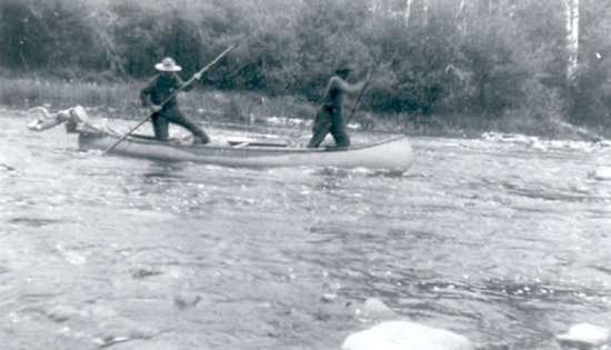 Fred Darbyshire and unidentified trapper<BR> poling a canoe in the rapids<BR>probably on the Foster River