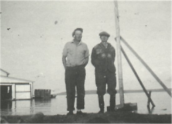 bernard johnson (left) and tom mcbride (right),<br>standing by the Old Fish Plant, August, 1951.