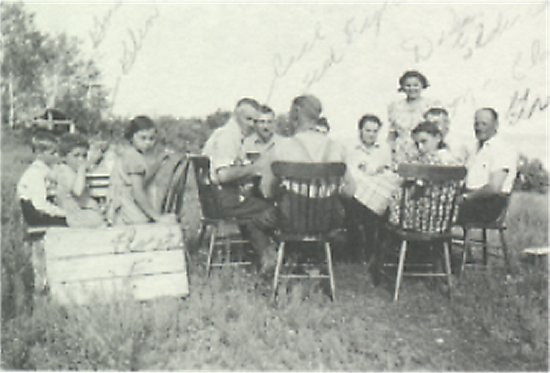The children are: Ted Johnson, Gordon, Glen and Florence Eldridge. Sitting around the table are: Carl Johnson, Ted Figeland, Delea Eldridge, Harold Eldridge, Verner Johnson and Connie Eldridge.