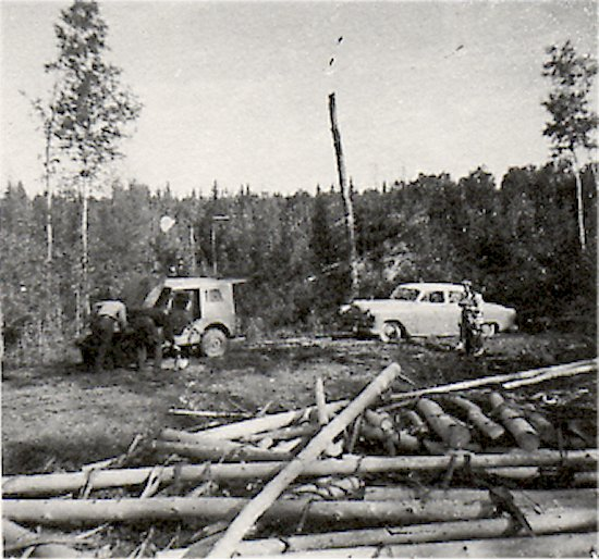 Dore Lake Road, 1952, between Appleby Creek and Sled lake Junction. Henry mason being towed by Clarence Williams Conservation Officers) Poles on the side of the road is used as pulp wood.