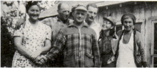 Front left: Mrs. George Mirasty holding Geir Thorden's hand.<BR> Back left: Verner Johnson beside Bob Roberts.<BR> Back far right: Mary McBride beside Miss Crow.<BR> In front of the cook shack at Waite's fish plant.