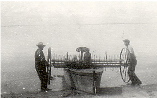 Verner Johnson and Les Christianson loading the hay rake to take to Grassy Point.