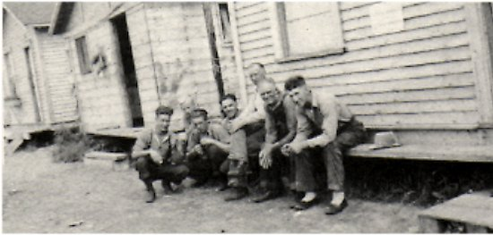 Waite's cabins built to house workers at the fish plant.<BR> Men seated on store step are waiting for the dinner bell. <BR>  From left to right: Jack Olson, Lloyd Snell, Orlon Olson, Dawson Beckett, Andrew Snell, Frank Johnson, Jake Belfrey.