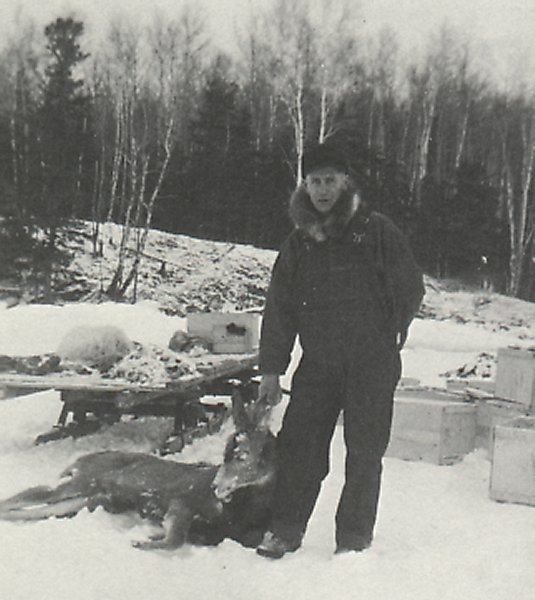 Stan Campbell with a deer, killed by timber wolves, close to his camp.