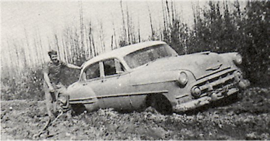 Dore Lake Road, 1952, near the forks of highway 55. Doug Wake (Saskatoon) stuck in mud.
